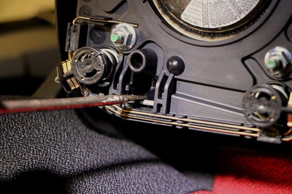 Detailaufnahme eines Schraubendrehers, der die auf der Rückseite des ausgebauten Airbags befindliche Klemme zur Seite drückt