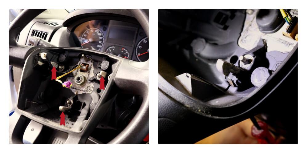 Detailaufnahme des Lenkrades mit ausgebautem Airbag und roten Markierungspfeilen, die die Widerhaken im Lenkrad markieren