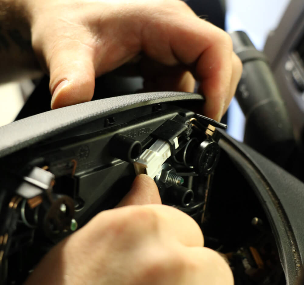 Detailaufnahme der Rückseite des Airbags mit einem Stecker, der herausgezogen wird