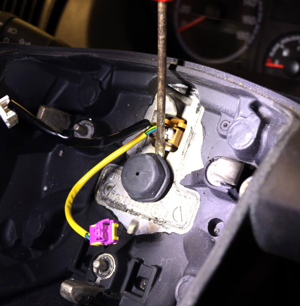 Detailaufnahme des Lenkrades mit ausgebautem Airbag und der zentralen Schraube, die Lenkrad und Lenkstange miteinander verbindet