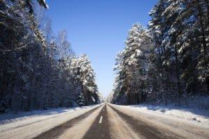 Blick auf eine Landstraße im Winter deren Fahrbahn zum Teil wieder vom Schnee freigefahren ist
