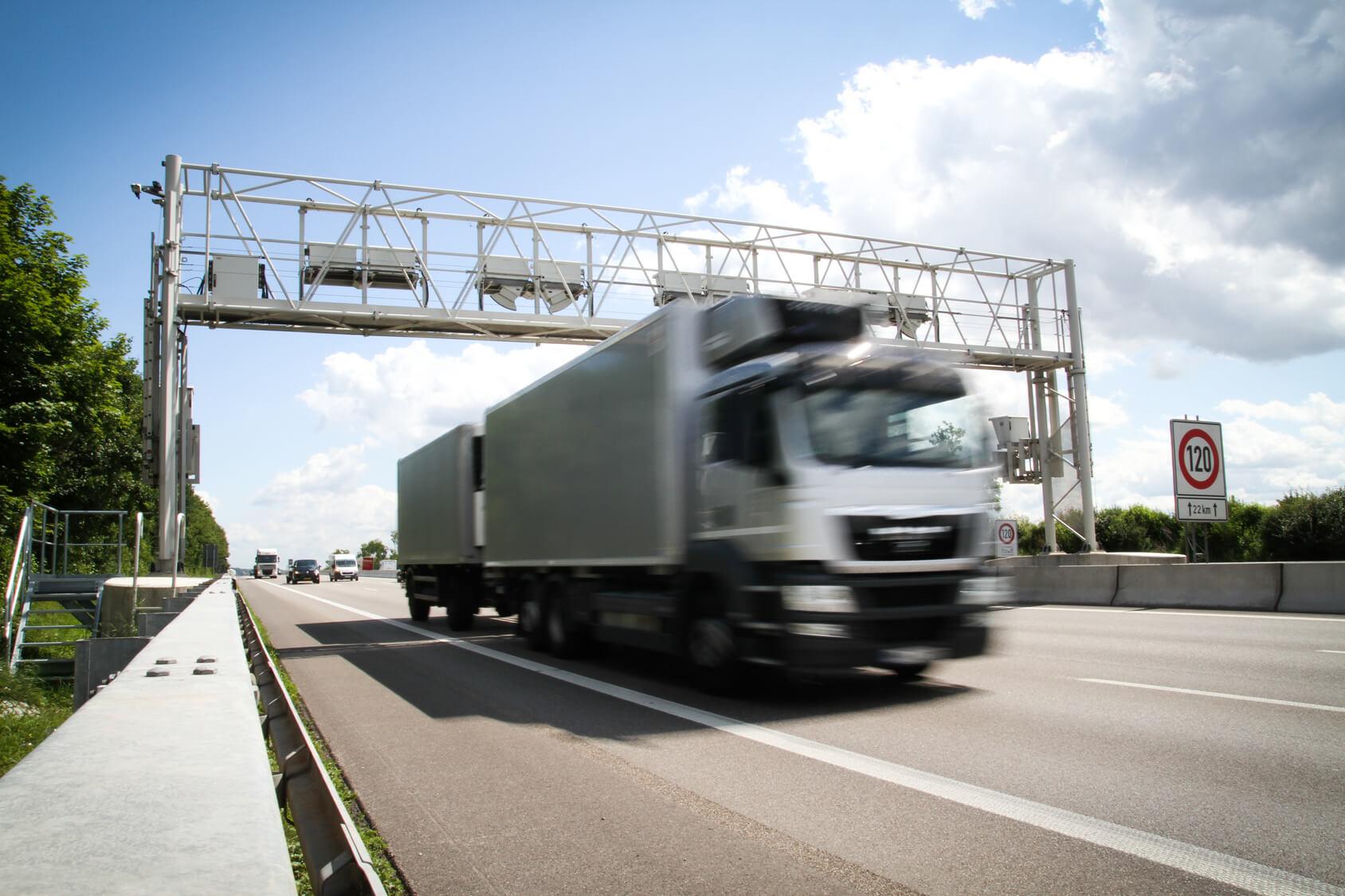 Lkw fährt auf einer Autobahn durch eine Maut-Erfassungsstelle.