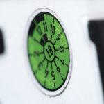 Die grüne TÜV-Plakette auf einem Nummernschild mit Tiefenschärfe fotografiert.