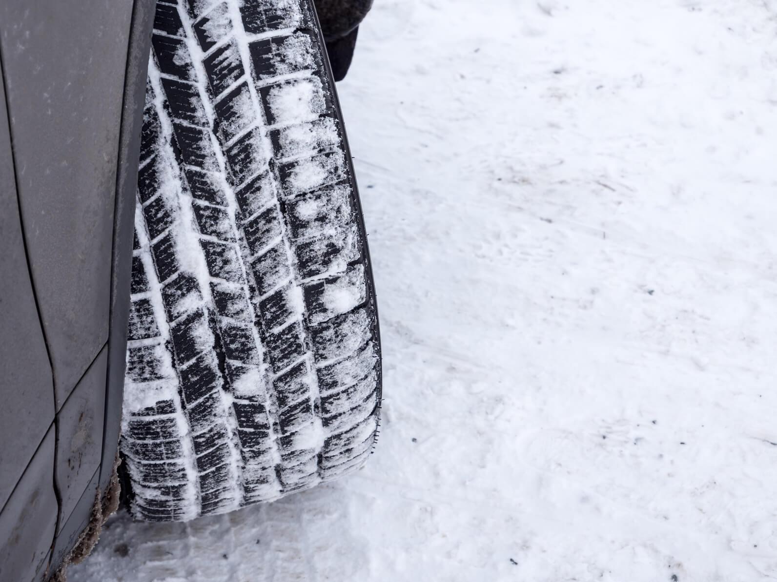 Winterreifens eines Pkw auf schneebedeckter Fahrbahn mit Schnee im Reifenprofil.
