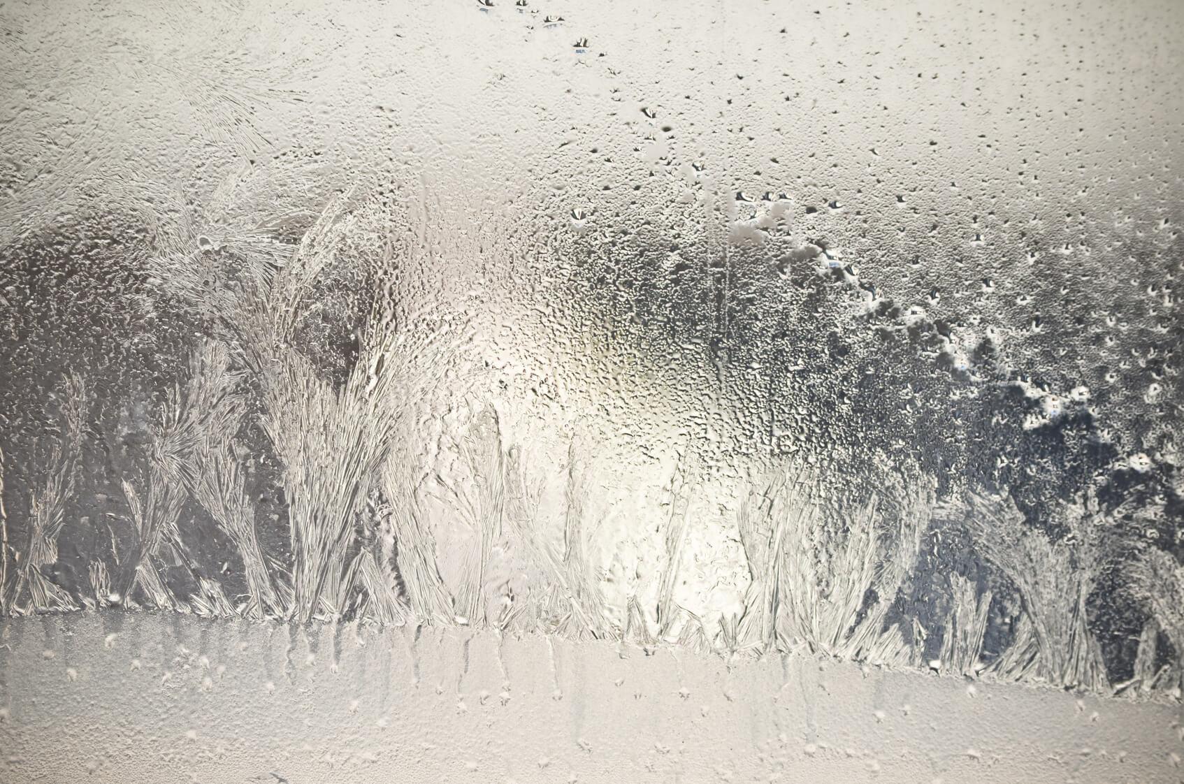 Blick durch eine verschmierte, halb zugefrorene Autoscheibe nach draußen.
