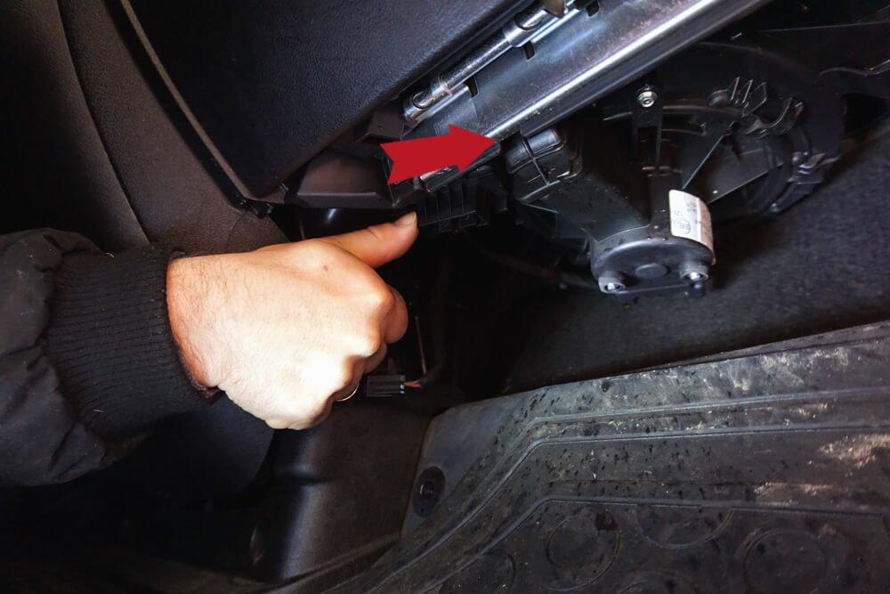 Foto einer Hand, die den Heizungswiderstand leicht nach rechts drückt; ein roter Pfeil im Bild markiert zusätzlich die Richtung.
