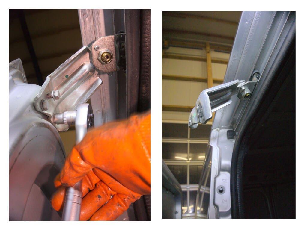 Detailaufnahme der Hand eines Mechanikers, wie er mit einer Knarre das oberste Scharnier mitsamt der Laufrollen von der Schiebetür löst.