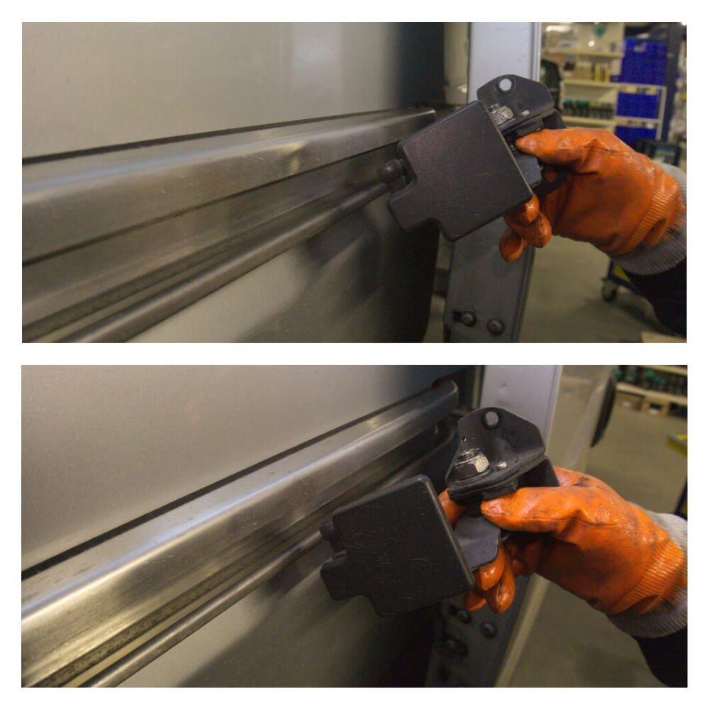 Detailaufnahme der Hand eines Mechanikers, wie das gelöste Scharnier schräg aus der mittleren Laufschiene herausdreht.