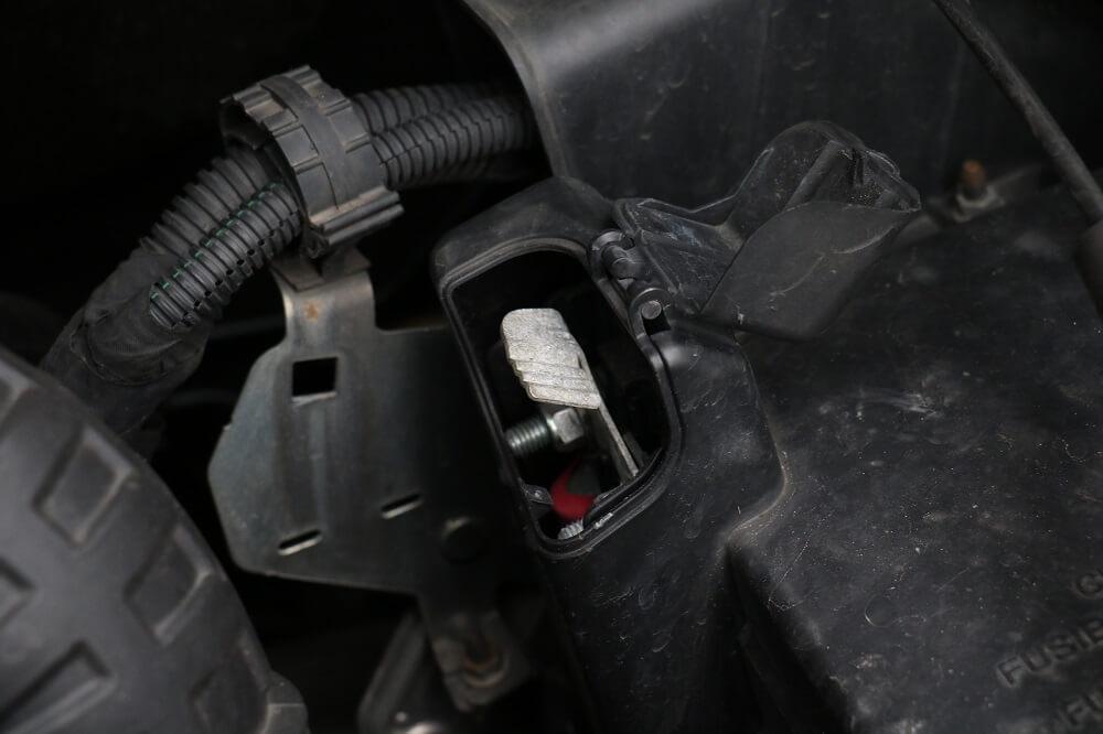 Schwarzer Plastikkasten im Motorraum des Fiat Ducatos mit aufgeklappter Klappe, hinter der der Pluspol für die Starthilfe zu sehen ist.