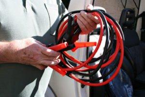 Halbtotale eines Mannes, der das schwarze und rote Kabel für die Starthilfe in seinen Händen hält.