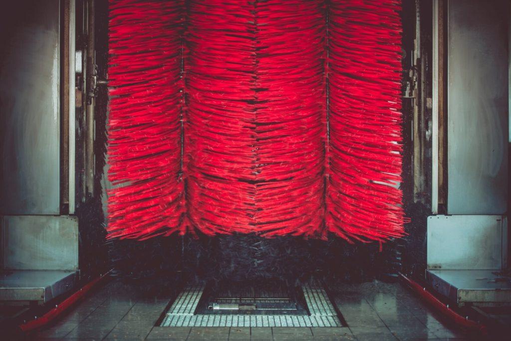 Blick von vorn in eine Waschanlage mit roten Waschbürsten, die gerade ein Auto reinigen.