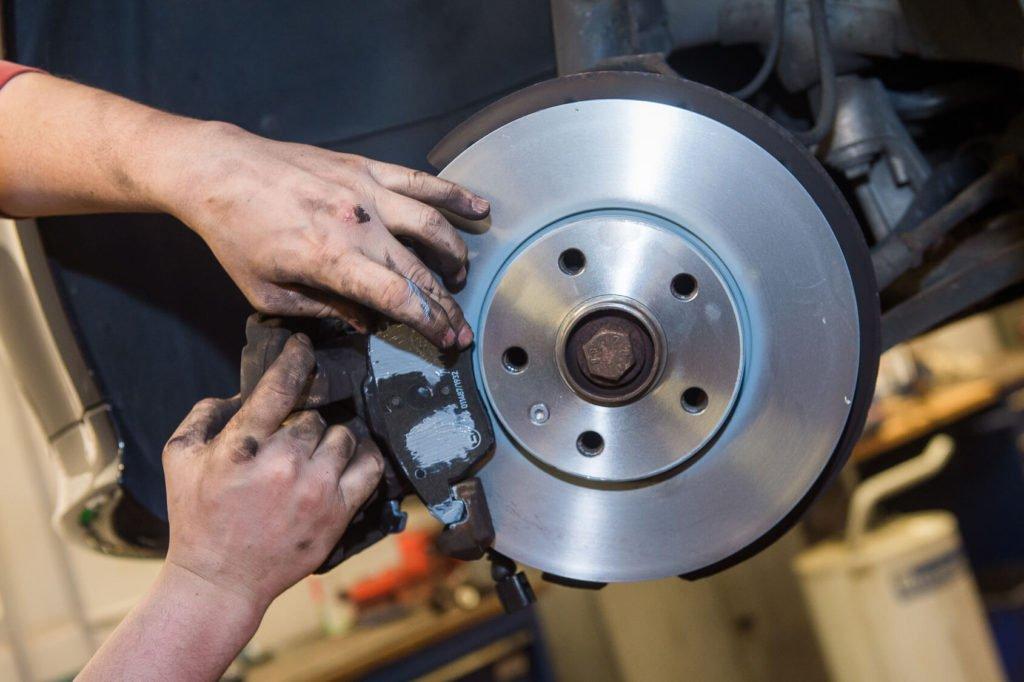Ein Kfz-Mechaniker wechselt die Bremsscheiben an einem aufgebockten Auto.