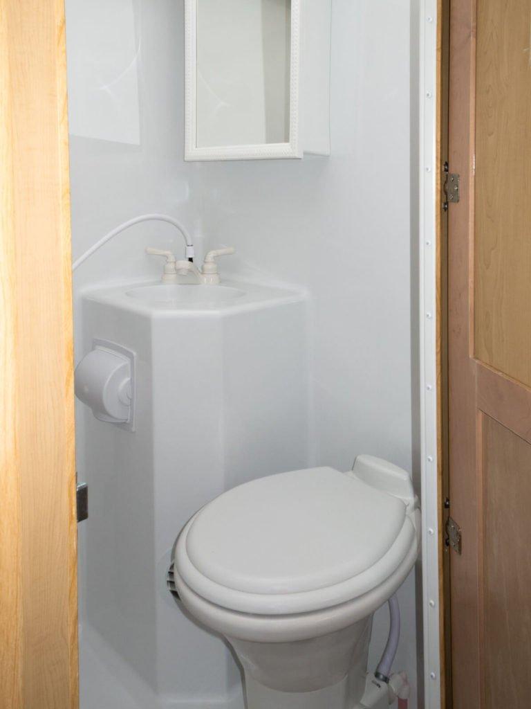 Der Sanitärbereich in einem Wohnmobil mit Waschbecken, Toilette und Spiegelschrank.