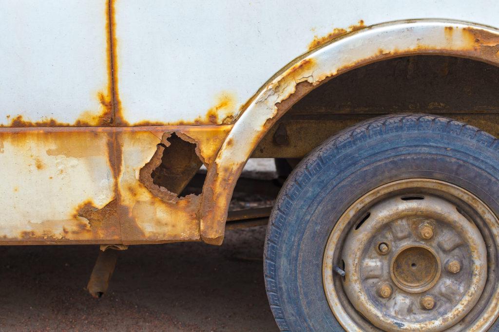 Detailaufnahme eines verrosteten Radkastens und von einem durchgerosteten Schweller.