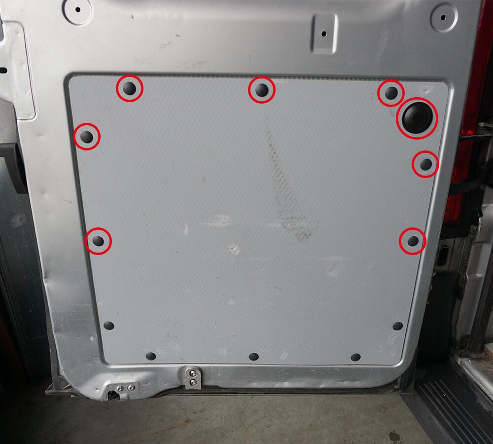 Die Verkleidung der Heckklappe mit den für den Ausbau herauszulösenden Plastiksicherungen, die mit roten Kreisen markiert sind.
