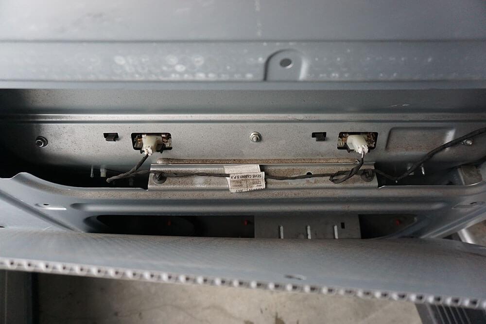 Blick hinter die Verkleidung der Heckklappe auf die Rückseite der Kennzeichenleuchte mit den beiden Steckern.