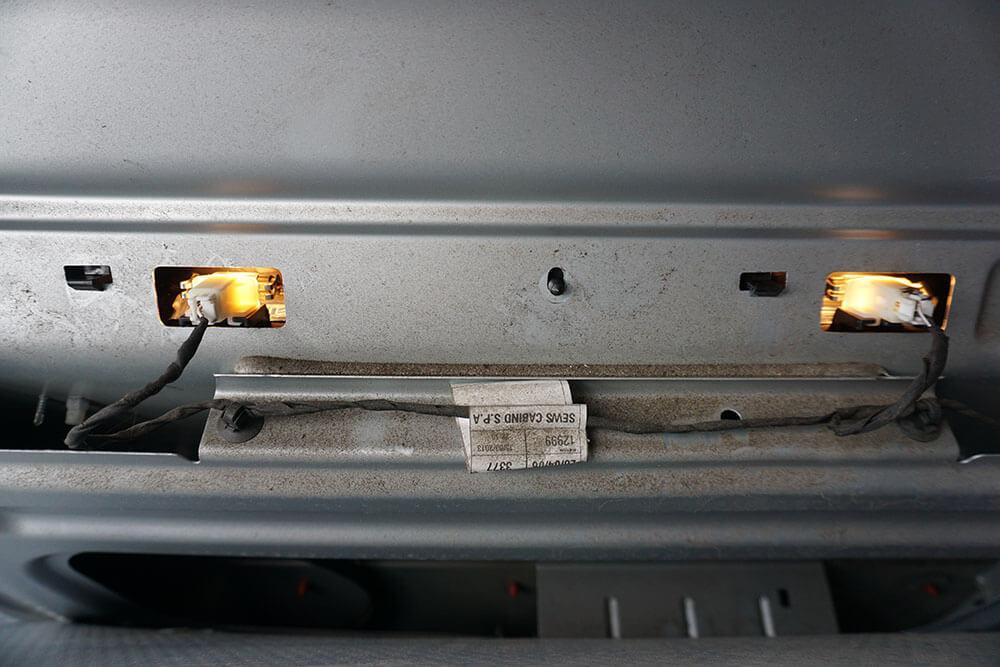 Die Rückansicht der eingebauten Kennzeichenleuchte mit zwei funktionierenden Lampen. Die Verkleidung der Heckklappe ist für die Aufnahme zurückgeklappt.