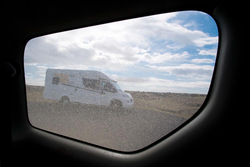 Durch ein dreckiges Fenster wird der Blick auf ein Wohnmobil vor blauem Himmel freigegeben.