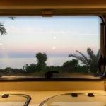 Aussicht auf einen Sonnenuntergang am Meer aus einem Wohnmobilfenster.