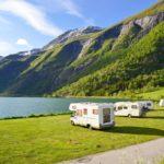 Mehrere Wohnmobile stehen auf einer grünen Wiese in der Sonne an einem See und Bergen.