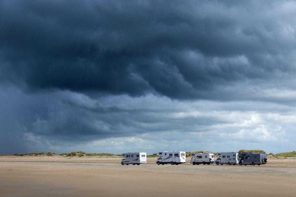 Dunkle Wolken über einer weiten Dünenlandschaft mit Wohnmobilen.