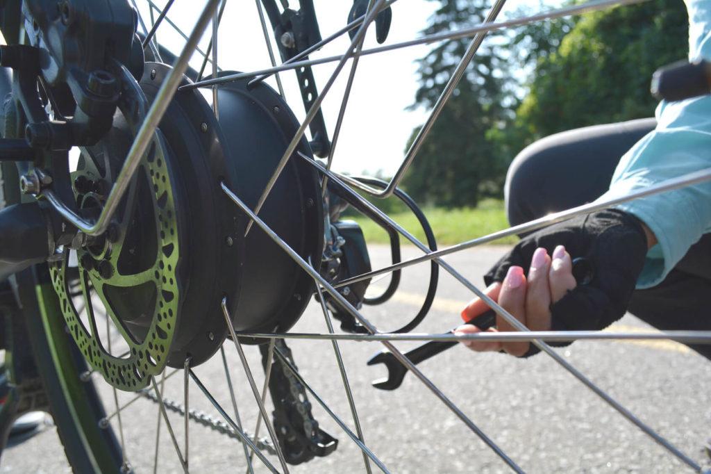 Fahrradspeichen und eine weibliche Hand mit Schraubendreher dahinter.