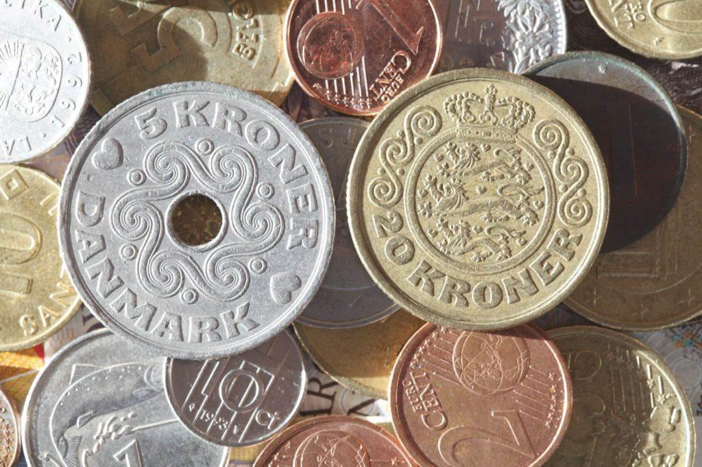 Verschiedene Währungen wie Kronen und Euro in Form von aufeinandergestapelten Münzen.