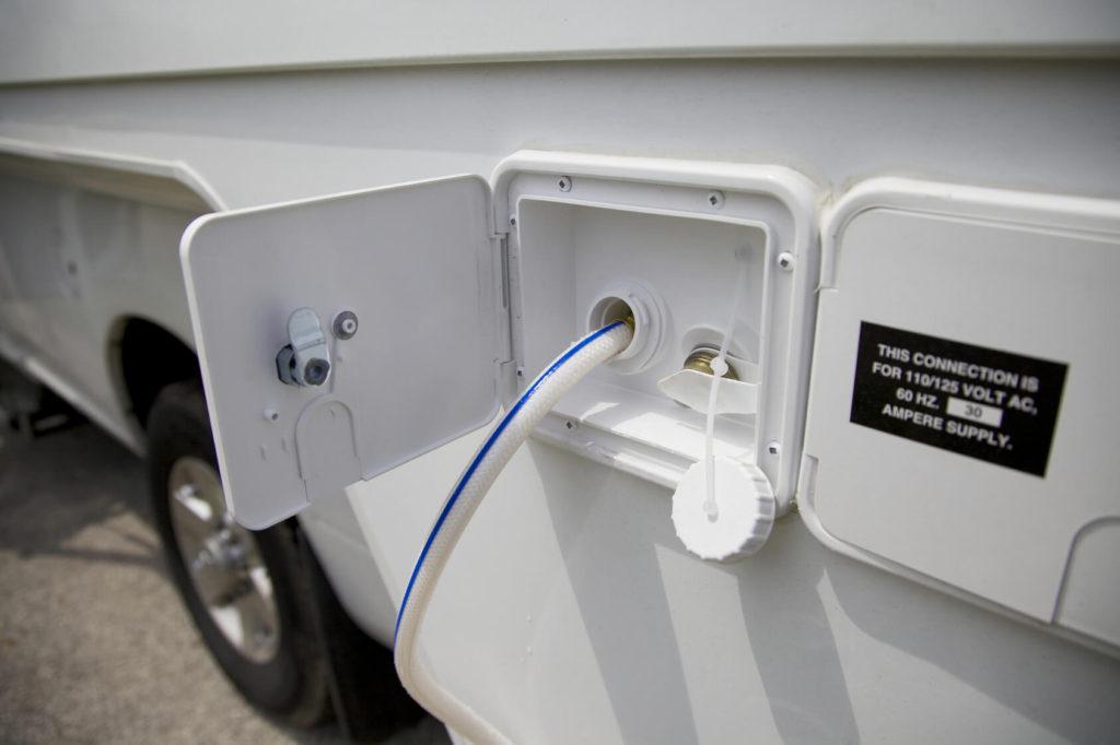 Wasser wird mit einem blau-weißen Schlauch aus einem Wohnmobil-Wassertank geleitet.