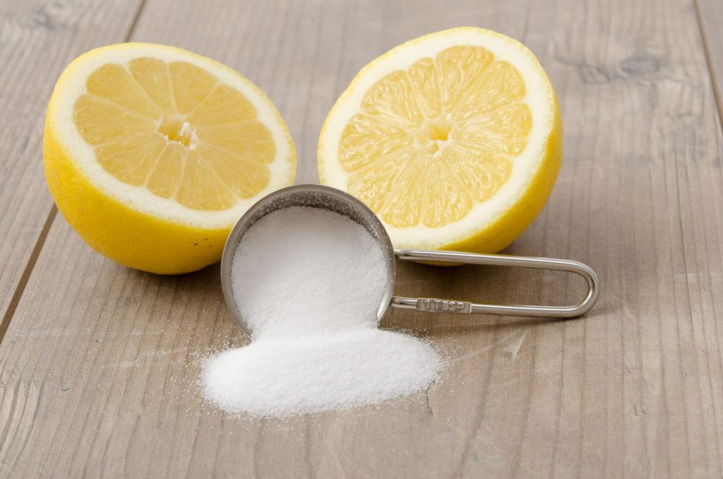 Zwei Zitronenhälften liegen neben einem Messlöffel mit weißem Pulver auf Holzuntergrund.