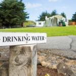 Ein weißes Schild mit der Aufschrift »Drinking Water« vor einem Campingplatz.