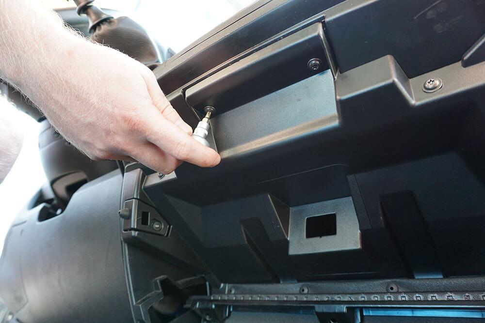 Ein Mechaniker löst mit einem Torx TX 20 zwei Schrauben zur Befestigung des Handschuhfaches im Fiat Ducato.