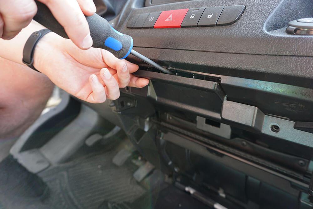 Ein Mechaniker drückt mit einem Schlitzschraubendreher vorsichtig die hintere Verkleidung des Handschuhfaches im Fiat Ducato heraus.