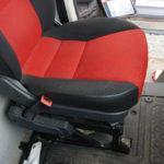 Vom Beifahrersitz aus fotografierter Fahrersitz im Fiat Ducato Typ 250 mit schwarz-rotem Bezug.