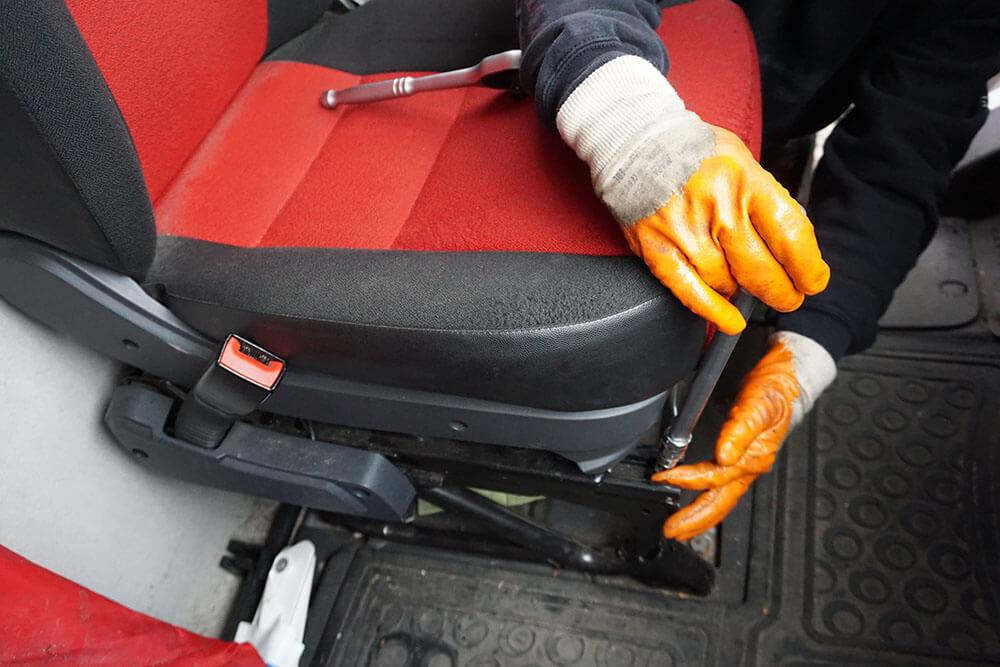 Ein Mechaniker dreht die vorne rechts sitzende Schraube in der Schiene des Fahrersitzes mit einem Torx T40 heraus.