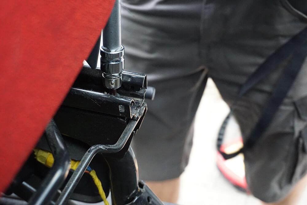 Nahaufnahme des Herausdrehens der vorne links sitzenden Schraube in der Schiene des Fahrersitzes; im Hintergrund die Beine des Mechanikers in kurzen Hosen.