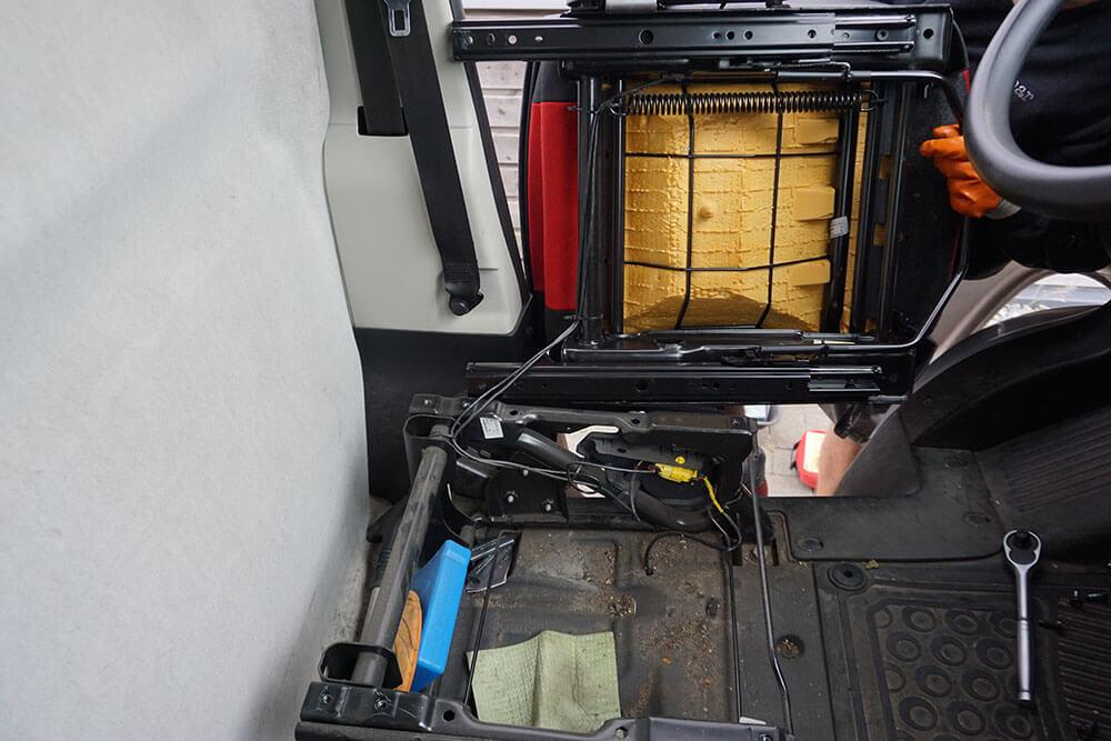 Die Unterseite des ausgebauten Fahrersitzes im Fiat Ducato Typ 250; der Mechaniker steht außen vor der Fahrertür und kippt den Fahrersitz zu sich, sodass die Unterseite sichtbar ist.