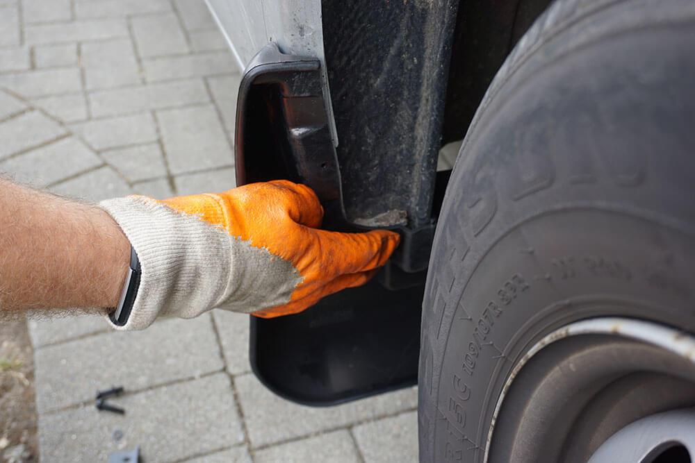Ein Mechaniker hält den zu montierenden Schmutzfänger testweise an den Kotflügel auf der Beifahrerseite eines Fiat Ducatos.