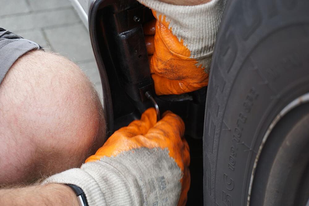 Ein Mechaniker drückt mit dem linken Knie den Schmutzfänger in Position, mit der rechten Hand schraubt er eine Klemme mit einem Inbusschlüssel fest.