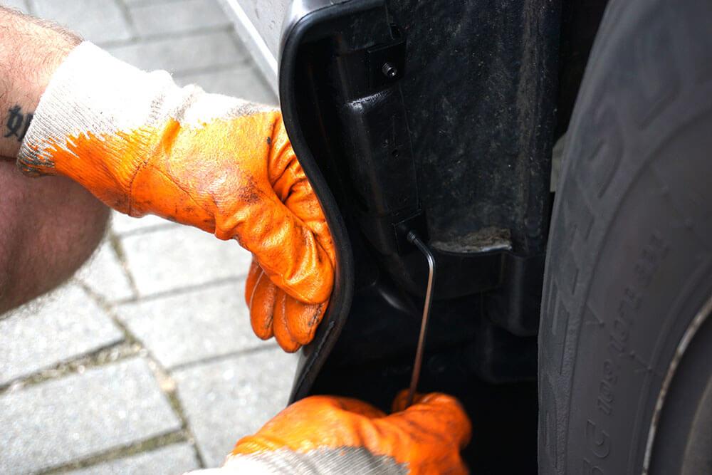 Ein Mechaniker drückt mit der linken Hand den Schmutzfänger in Position, mit der rechten Hand schraubt er eine Klemme mit einem Inbusschlüssel fest.