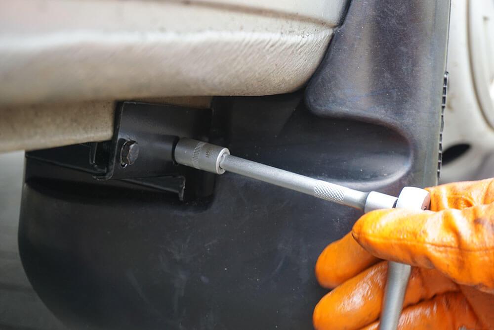 Nahaufnahme der unteren Klemme des Schmutzfängers, die ein Mechaniker mit einer 10 mm Nuss festzieht.