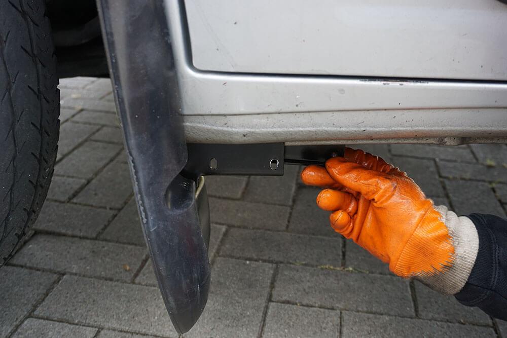 Nahaufnahme der unteren Klemme des Schmutzfängers auf der Fahrerseite, die ein Mechaniker in Position drückt und festschraubt.