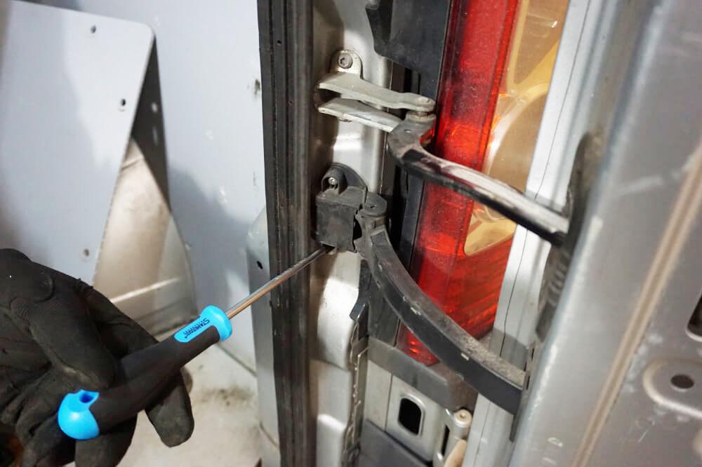 Die Schrauben der Hecktür-Gelenks werden mit einem Kreuzschlitzschraubendreher herausgedreht.