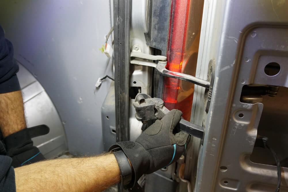 Ein Mechaniker zieht das Hecktür-Gelenk aus der Karosserie.