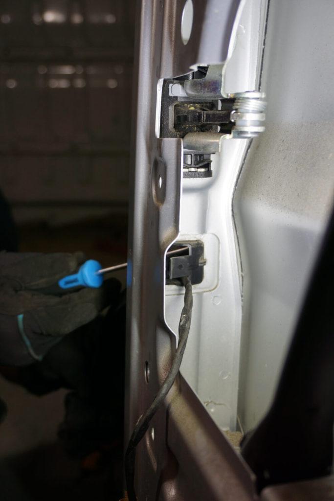 Ein Mechaniker drückt mit einem Kreutzschlitzschraubendreher die Plastiksicherung heraus, durch die der Hecktür-Kabelbaum sich nicht aus der Hecktür lösen kann.