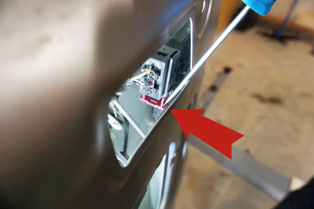 Detailaufnahme des roten Steckers, der den Hecktür-Kabelbaum mit der Nummernschildbeleuchtung verbindet; ein roter Pfeil markiert, dass der Stecker nach unten herausgedrückt werden muss.