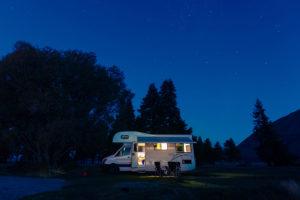 Ein Wohnmobil steht einsam bei Nacht an einem Waldrand.