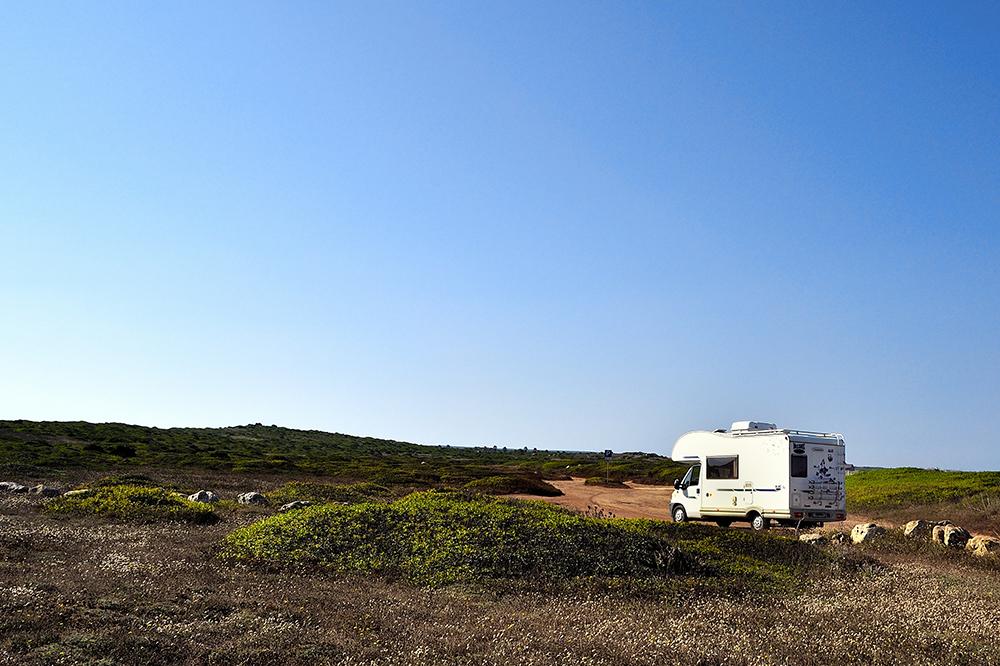 Ein Wohnmobil in einer flachen, einsamen Landschaft.