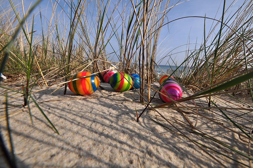 Bunte Ostereier zu Ostern am Strand auf Rügen.