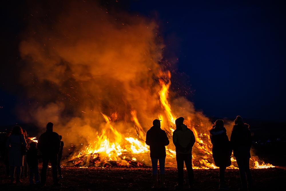 Einige Menschen zeichnen sich vor einem nächtlichen Osterfeuer ab.