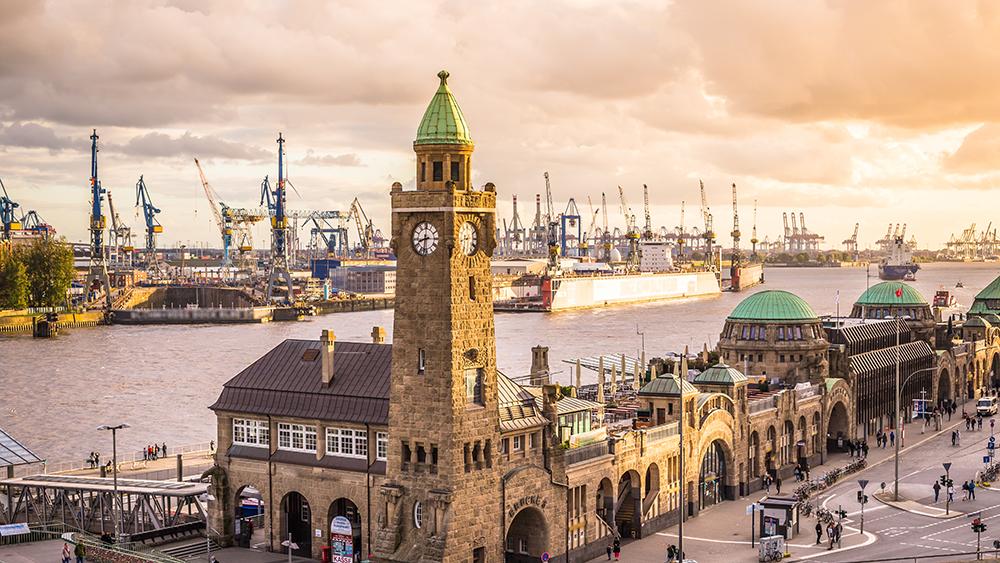 Die Landungsbrücken in Hamburg werden in abendliches Licht getaucht.